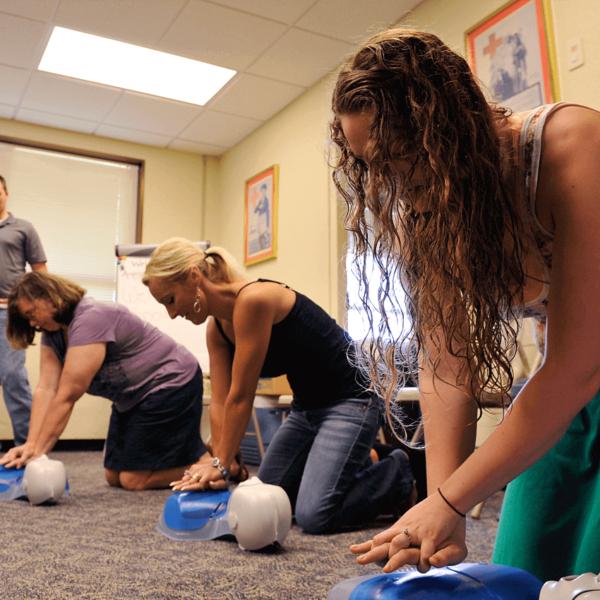 grupo de mmujeres realizando maniobra de masaje cardiaco a muñeco de practicas