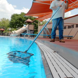 Personal de mantenimiento de piscinas limpiando con cazamariposas