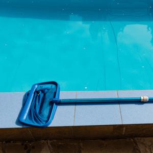 limpiafondos en el bordillo de piscina a modo de muestra , con fondo de agua cristalina