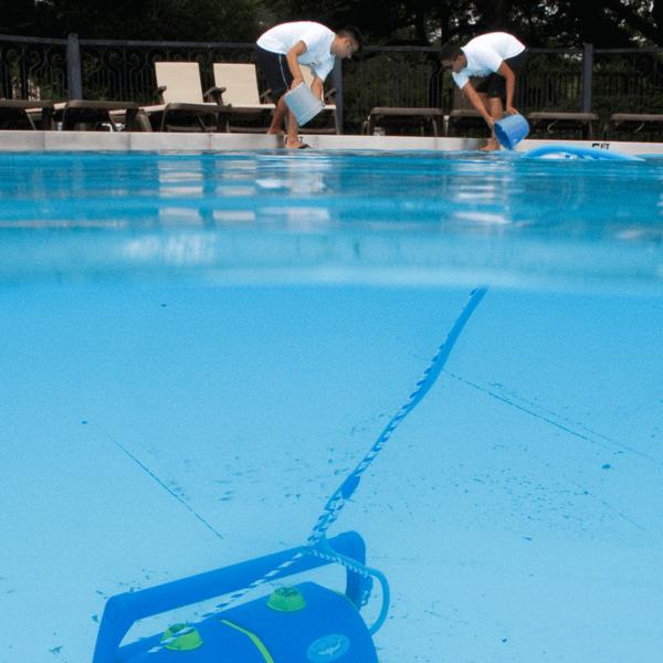 Dos tecnicos de mantenimiento limpiando la playa de la piscina