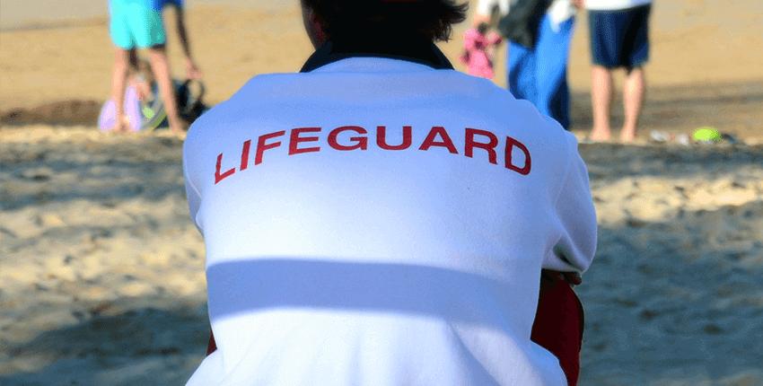 espalda de socorrista sentado vigilando en la playa en posicion sentada