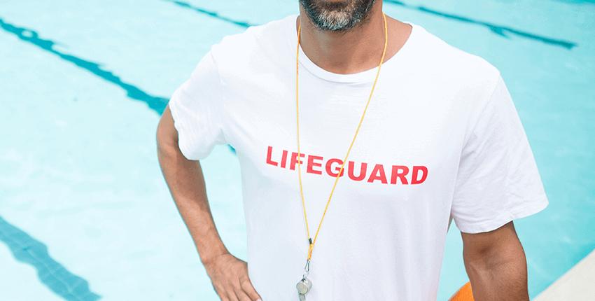 salvavidas con barba y visera parasol sonrie con lata de rescate amarilla en mano izquierda en el borde de una piscina de verano sin publico