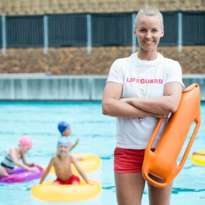 vigilante de piscina sexo chica sonriente con brazos cruzados y con lata de rescate, de fondo niños jugando en el agua de la piscina que vigila