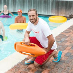 rubio sonriente guaperas socorrista de cuclillas en el borde de piscina con actividad acuatica