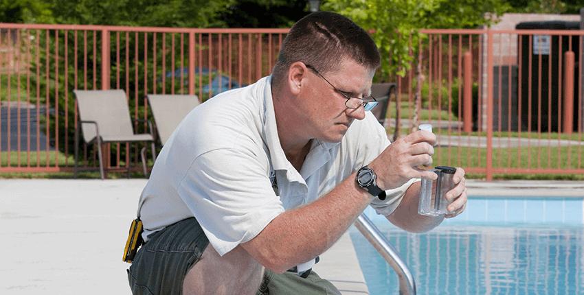 piscinero toma medidas de agua con aparato de medicion de cloro