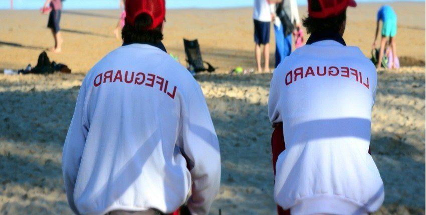 vista de las espaldas de dos socorristas de playa sentados y vigilando la orilla