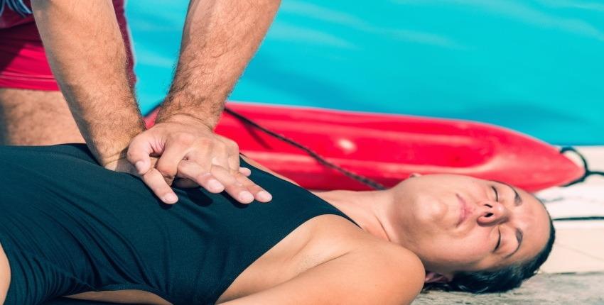 detalle de manos realizando maniobra de amasaje cardiaco a una victima chica en el borde de una piscina