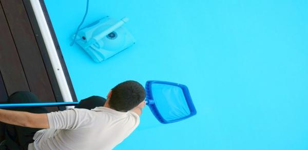 tecnico pasando caza mariposas mientras robot limpia el fondo de la piscina