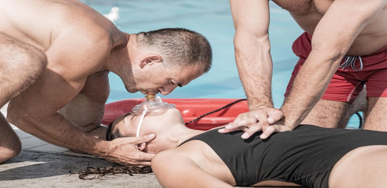 representacion de maniobra de respiracion artificial boca a boca con mascarilla de autoproteccion, un segundo socorrista aplica manos en torax para simular masaje cardiaco
